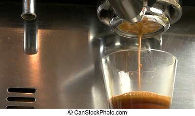 Espresso pouring from coffee machine. Glass with hot...
