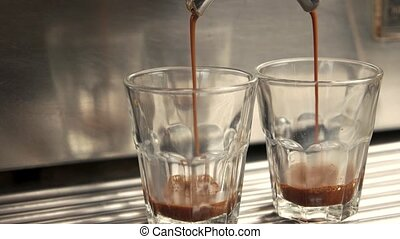 Coffee maker filling glasses. Coffee with foam, side view.