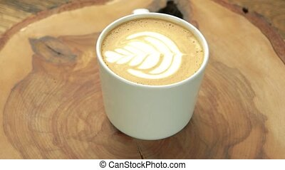 Close up of latte cup. Coffee beverage on wooden board.