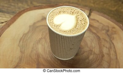 Heart latte art, paper cup. Coffee drink on wood board. Love...