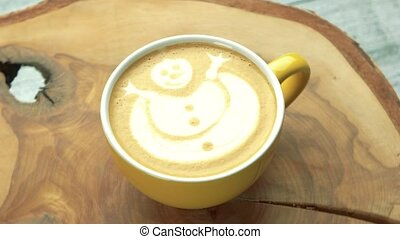 Coffee cup with snowman art. Latte on wooden surface.