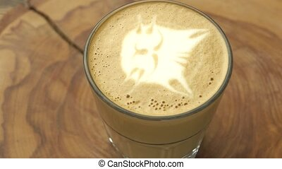 Latte glass with cat art. Coffee on wooden board spinning....