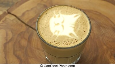 Cat face latte art. Glass with coffee beverage.