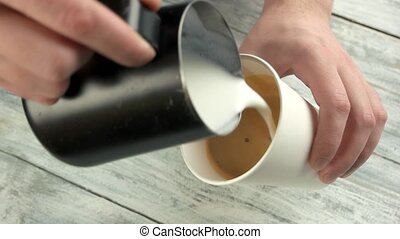 Man pouring latte art. Frothy coffee in paper cup.