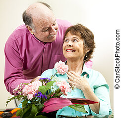 Flowers For His Lady - Handsome mature man presents flowers...