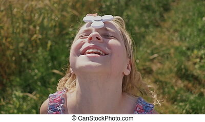 School kid girl playing with Hand Spinner outdoors. Spinner spins on the girl's forehead. Popular and trendy toy for hands for children and adults.