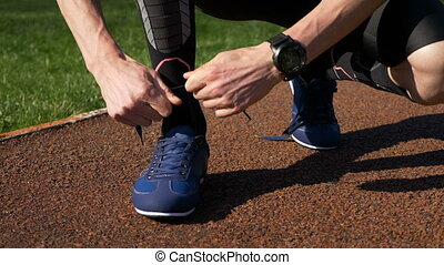 Fit jogger tying both shoelaces before running practice on...