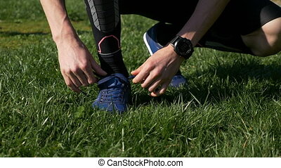 Closeup of athlete man tying shoelaces before jogging in the...