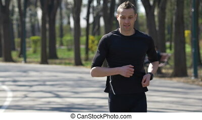 Closeup of fit jogger stopping from running in park checking smartwatch fitness tracker