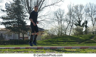 Athletic man doing legs exercises in park and warming up...