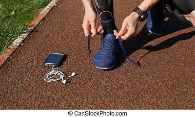 Closeup of runner tying shoelace then picking up smartphone...