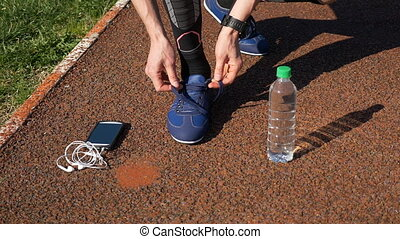 Jogger with smartwatch tying shoelaces and picking up...