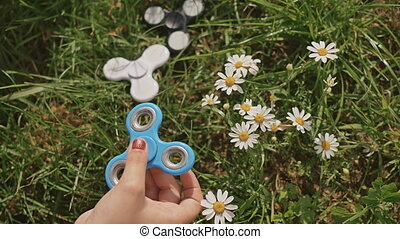 Young girl playing with a blue spinner on the lawn on a summer sunny day.