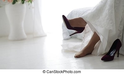 Bride in a beautiful wedding dress putting on shoes. Bride...