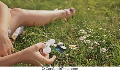 Young girl playing with a white spinner on the lawn on a summer sunny day.