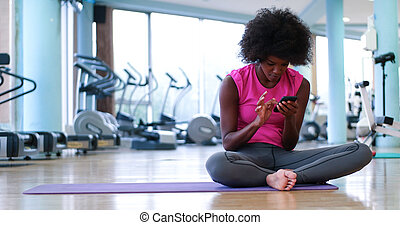 portrait of young afro american woman in gym on workout...