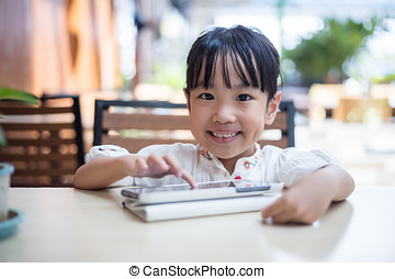 Asian Chinese little girl playing tablet computer
