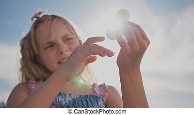 A young bright girl shows a spinner against the background...