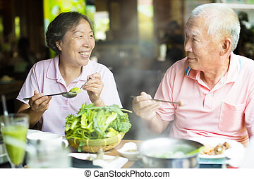 happy Senior Couple Enjoying hot pots In Restaurant