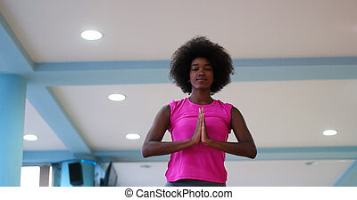back woman in a gym stretching and warming up