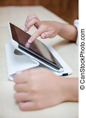 Child's hands playing tablet computer
