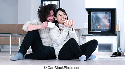 multiethnic romantic couple in front of fireplace - Young...
