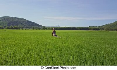 Aerial View Girl Sits in Yoga Pose on Rice Field by Hills -...