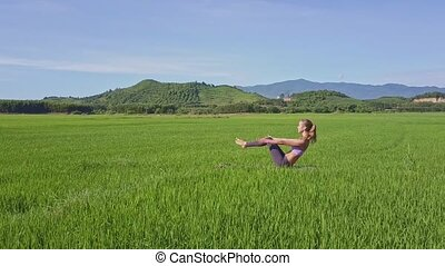 Drone Shows Girl Doing Yoga against Green Hills Clear Sky -...