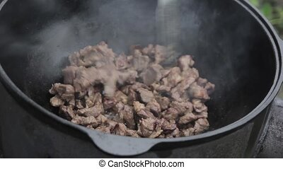 Cooking of pilaff with lamb and onions in a cauldron on a wood stove