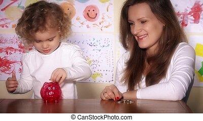 Babysitter and little cute child girl putting coins into piggy bank