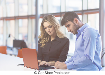 Young couple working together on a laptop in the office....