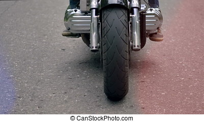 Close up of a motorcycle front wheel turning.