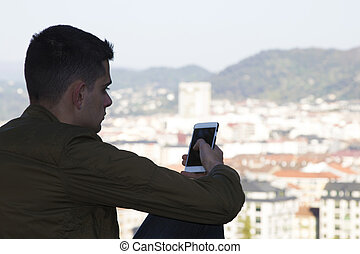 silhouette of the teenager with the mobile phone and the city in the background