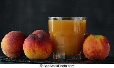 Close-up of peach juice poured into a glass, black...