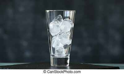 Cola and ice in glass. Cola pouring into a glass with ice...