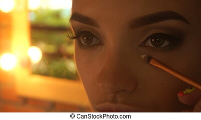 makeup artist with a brush cleans black eyes girl close-up
