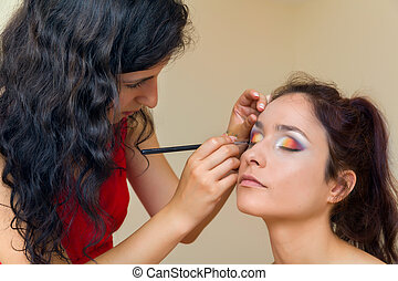 Professional make-up artist working on a photo model's face