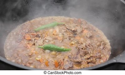 Cooking of pilaff with lamb. Meat with vegetables and hot...