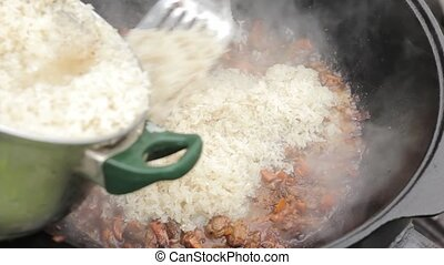Cooking of pilaff with lamb, carrots and spices onions in a...