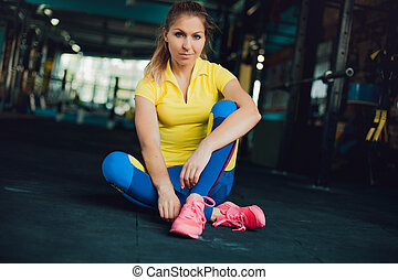 Girl in fitness club. Young female athlete sitting on floor...
