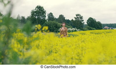 Young woman walking in a flower field. Beautiful landscape summer flower field