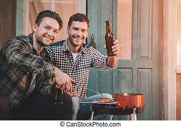 happy young friends making barbecue and drinking beer on porch with back light