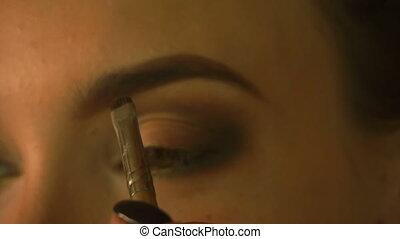 young girl makes eye makeup