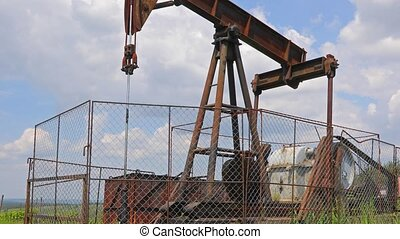 Oil well on a landscape - Old rusty oil well on a field