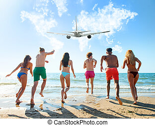 Group of friends run to the sea with an aircraft in the sky....