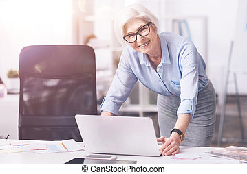 Prominent mature business lady using her laptop - Familiar...