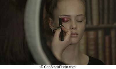 Beautiful young girl with a stylist doing extreme makeup in a beauty salon