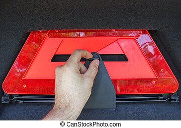 A man hand pulls out a red folded emergency sign lies from the trunk.