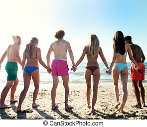 Group of friends hold hands to one another on the seashore