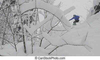snowboarder Freerider rides in the forest